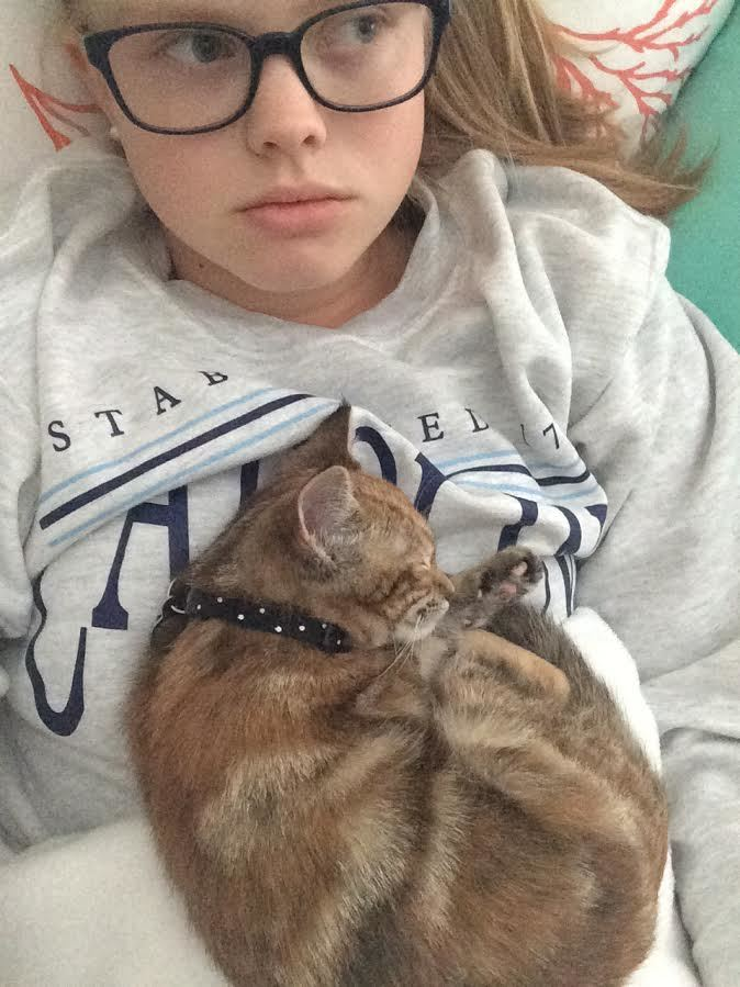 Small kitten sleeps on the chest of a girl in glasses.