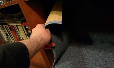 Hand attaching carpet to inside of bookshelf.