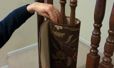 Hand attaching flowered area rug to staircase spindle.